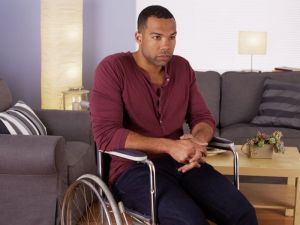 African man sitting in wheelchair looking at camera